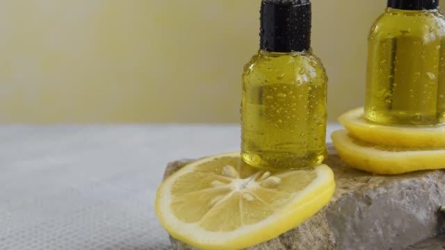 vídeos de stock, filmes e b-roll de garrafas com óleo de limão essencial. tratamento de beleza natural saudável - aromaterapia