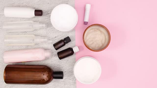 bottiglie con prodotti cosmetici per la cura della pelle si muovono sul tavolo stop motion - mercanzia video stock e b–roll
