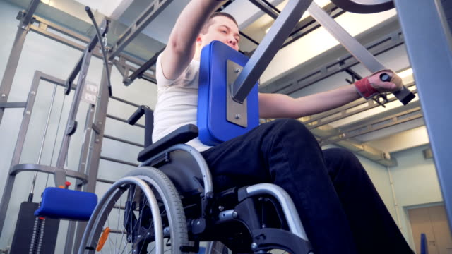Bottom view of an lift-weighting exercising process of a disabled man video