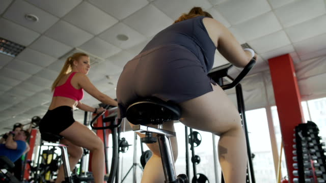 Bottom view of obese female working at stationary bike in the sports club video