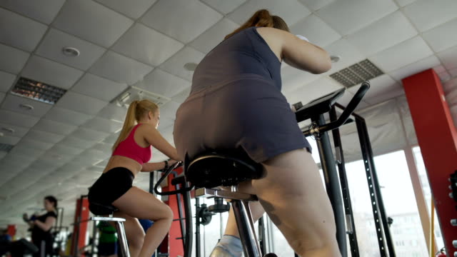 Bottom view of overweight lady riding stationary bike at sports club, fitness video