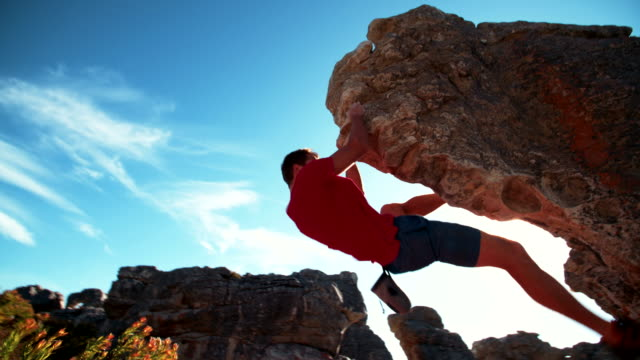 Bouldering rock climber hanging beneath extreme overhang against blue sky video