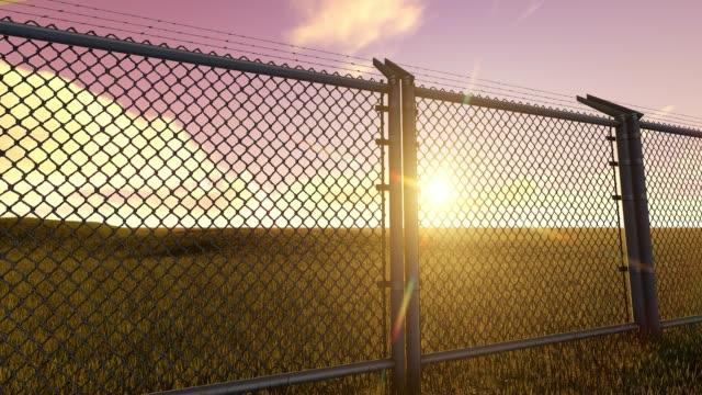 vídeos de stock e filmes b-roll de boundary fence on sunrise - cercado