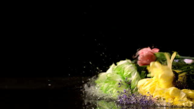 Bouquet of flowers falling onto wet black surface video