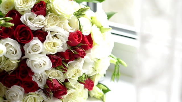 bouquet of red and white roses lies at the window, beautiful colorful flowers are on the table. - pistillo video stock e b–roll