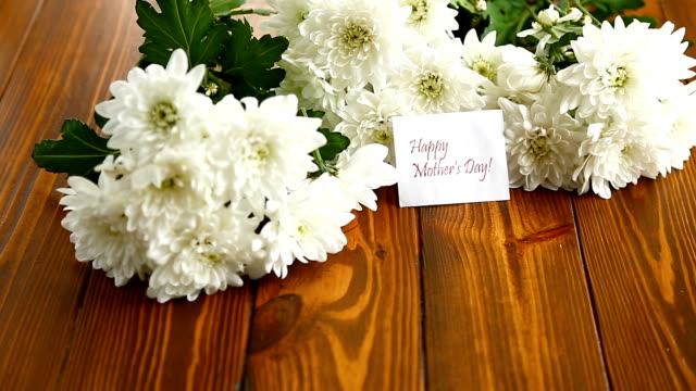 bouquet of white chrysanthemums on wooden table video