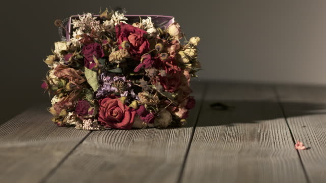 bouquet of withered flowers on wooden table. dried flower arrangement - bouquet video stock e b–roll