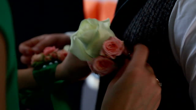 a boutonniere flower arrangement being pinned to a shirt for the prom - prom stock videos and b-roll footage