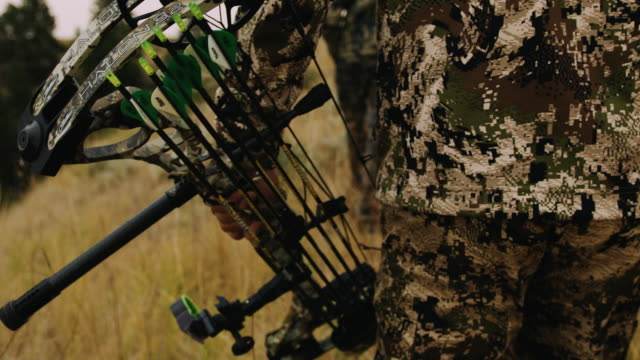 A bow hunter walks through grass carrying his compound bow, the shallow depth of field and slow motion give the shot a feeling of intensity as he walks in full camouflage.