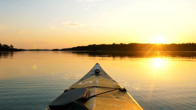 bogen von kajak schwimmt auf ruhiger oberfläche des twassers bei sonnenuntergang in golden erdstunde, outdoor-aktivitäten - kanu stock-videos und b-roll-filmmaterial