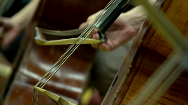 bow on a cello string in orchestra video
