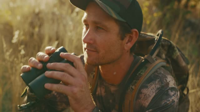 bowhunter takes a closer look through his binoculars - cacciatore video stock e b–roll