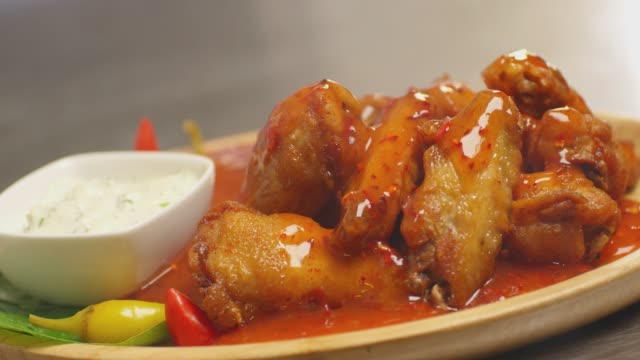 4K Bowl of buffalo wings with red and spicy sauce . Hot sauce pouring on chicken wings. Liquid pepper sauce pouring on chicken juicy meat into restaurant . Shot on RED Cinema camera in slow motion .