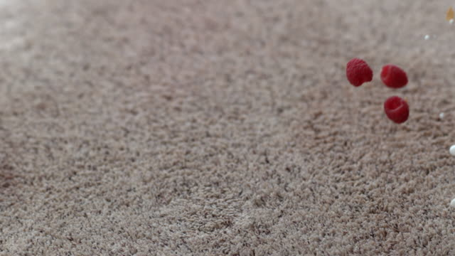 Bowl of cereal and raspberries spilling on carpet in slow motion video