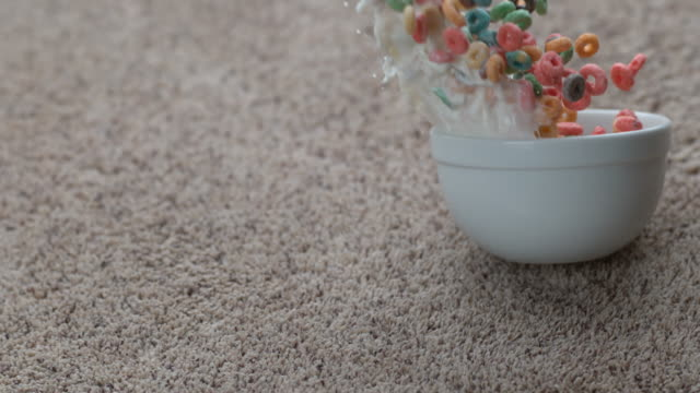 Bowl of cereal spilling on carpet in slow motion video
