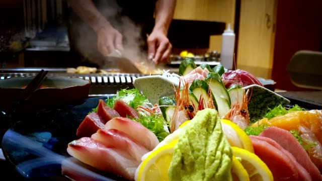 A bowl of fresh sashimi with a chef cooking in the background