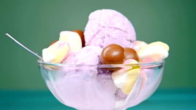 bowl of fresh sweet potato flavor ice cream sundae mixed with chocolate candy and marshmallows rotating - vídeo