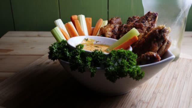 A Bowl Of Healthy Baked Grilled Chicken Wings Accompanied By Hot Sauce Celery and Carrot Sticks With A Beer A delicious bowl o Keto hot wings served with a cup of hot sauce, carrot and celery sticks garnished with parsley, with a frosty cold beer dipping sauce stock videos & royalty-free footage