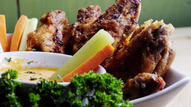 A Bowl Of Healthy Baked Grilled Chicken Wings Accompanied By Hot Sauce Celery and Carrot Sticks A delicious bowl o Keto hot wings served with a cup of hot sauce, carrot and celery sticks garnished with parsley tray stock videos & royalty-free footage