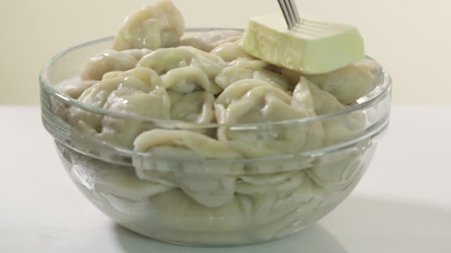 Bowl of homemade boiled dumplings with butter. Traditional Russian dish pelmeni Bowl of homemade boiled dumplings with butter. Traditional Russian dish pelmeni filled with meat. ravioli stock videos & royalty-free footage