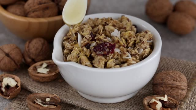 vídeos de stock e filmes b-roll de bowl of homemade granola with nuts. copy space - mel