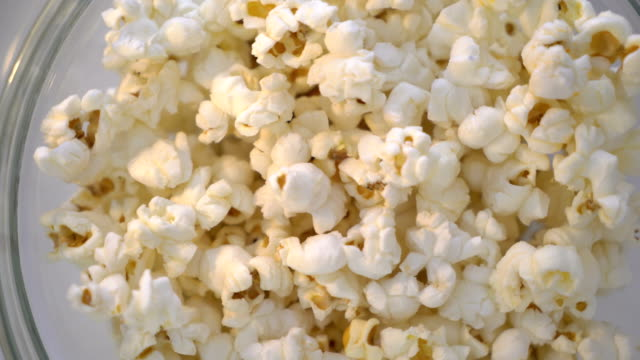 Bowl of popcorn turning around top view. Popped popcorn closeup. Bowl of popcorn turning around top view. Popped popcorn closeup. snack stock videos & royalty-free footage