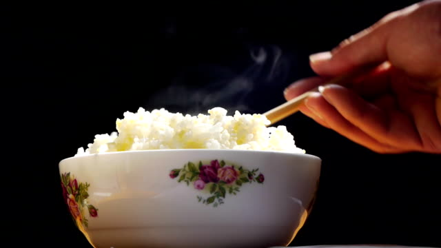 bowl of rice with hot. - ris spannmålsväxt bildbanksvideor och videomaterial från bakom kulisserna