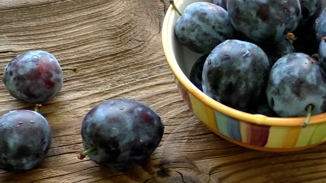 A bowl of ripe blue plums on a dark wooden background video