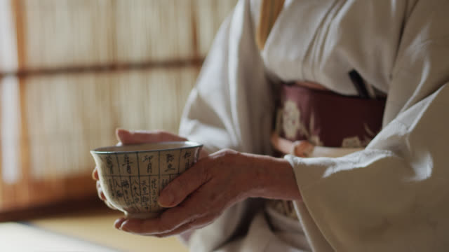 Bowl of Tea Steaming in Hands of Japanese Tea Ceremony Host