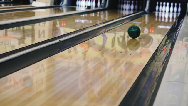 Bowling. A bowling player knocks out a strike.