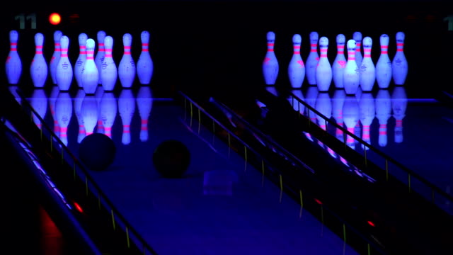 Bowling ball knocking down pins