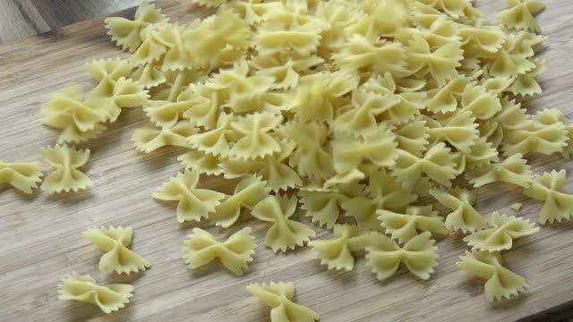 Bow-tie macaroni Farfalle pasta falling to a cutting board uncooked pasta stock videos & royalty-free footage