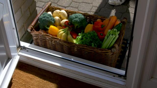 bir kutu meyve ve sebze eve teslim ediliyor. - sahanlık stok videoları ve detay görüntü çekimi