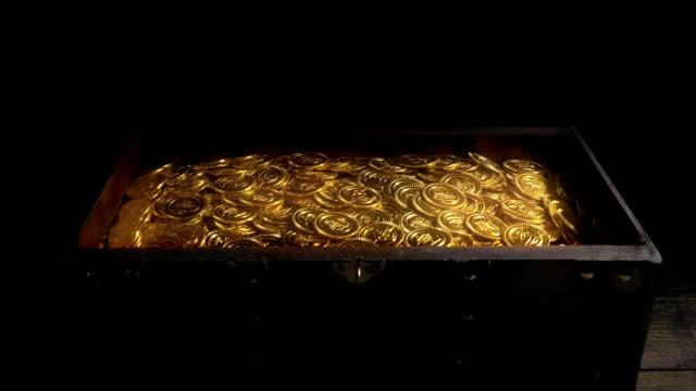 la scatola si apre e si chiude piena di monete d'oro incandescenti - scatola del tesoro video stock e b–roll