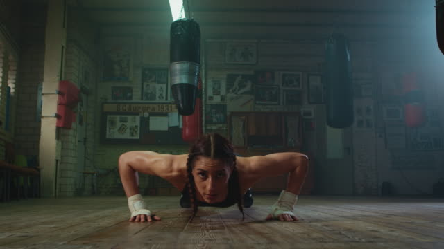 Boxer doing push ups A boxer doing push ups in an old gym. There are some punshing bags hanging in the background and old boxing posters on the wall. There is some haze in the air. The camera is on the ground. push ups stock videos & royalty-free footage