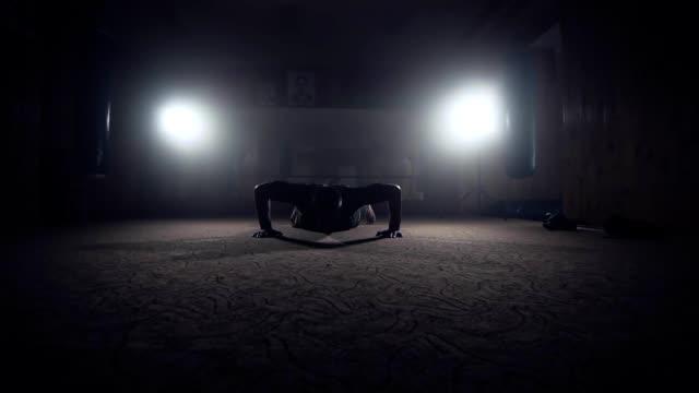 Boxer doing push-ups in dark smoky gym. Silhouette of athlete on dark background