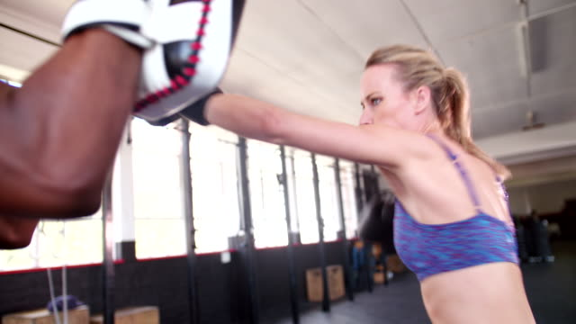 Boxer girl punching with her sparring partner at the gym video