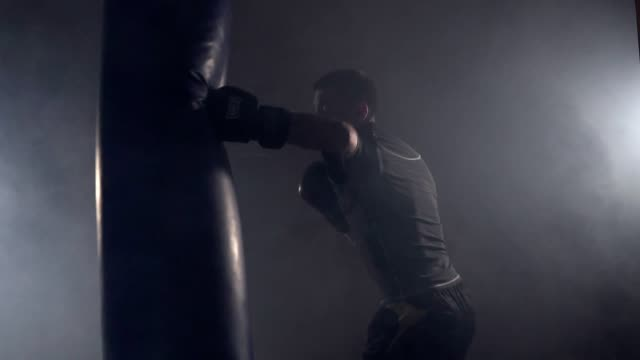 boxer hits punching bag in dark gym in slow motion. young man training indoors - sacco per il pugilato video stock e b–roll