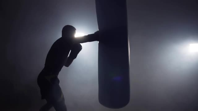 boxer hits punching bag in dark gym in slow motion. young man training indoors - box video stock e b–roll
