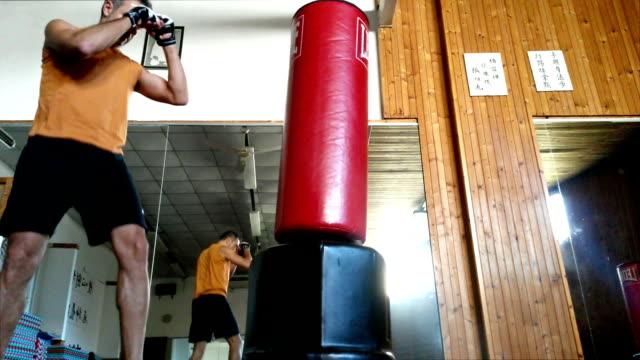 Boxer hitting the sandbag at mirror of gym video