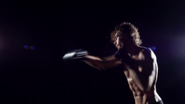 boxer in dark throwing flurry of fast punches - sparring throwing combinations - sparring allenamento video stock e b–roll