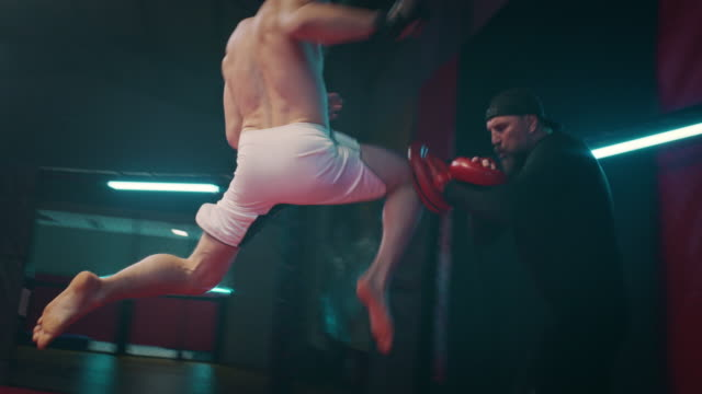 boxer pad work session with trainer. high kick with jump - sacco per il pugilato video stock e b–roll