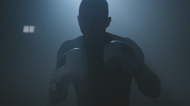 Boxer punching to camera. Silhouette of young boxer practicing boxing punches