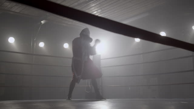 Boxer training in boxing ring, silhouette