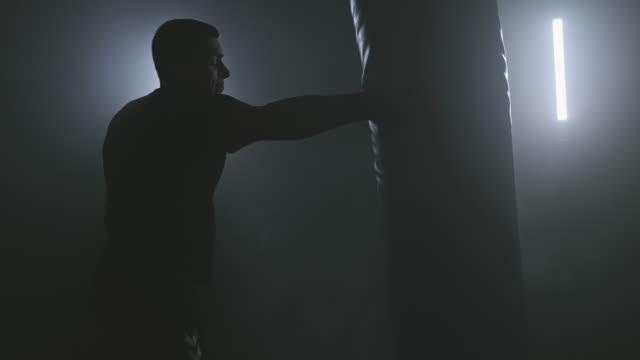 allenamento boxer in palestra in condizioni di scarsa illuminazione. sagoma dell'uomo che colpisce un sacco da boxe. - sacco per il pugilato video stock e b–roll