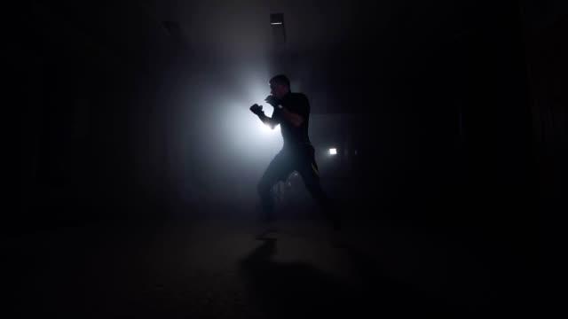 Boxer training in smoky studio. Sportsman boxing in dark gym