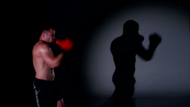 Boxer training shadow boxing over black background video