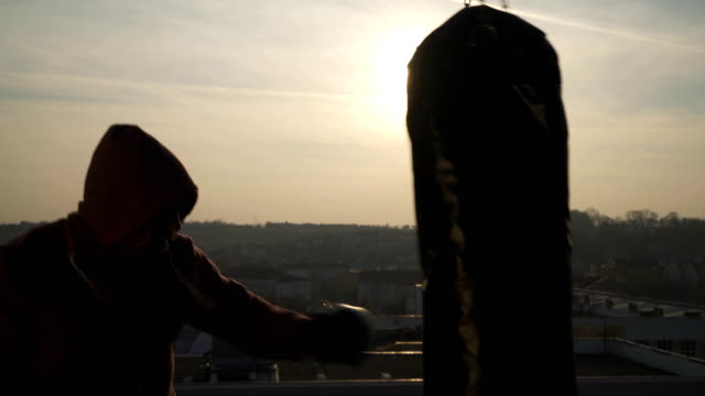 boxer with fighting gloves stands in guard punches bag in sunset, close up, city, sportsman practicing, power training, strong guy hard exercising, strength exercises, workout, handheld, sunny day. - colpire con un pugno video stock e b–roll