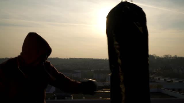 vídeos y material grabado en eventos de stock de boxeador con la luchando guantes puestos en guardia golpes bolsa en puesta del sol, cerca, ciudad, deportista practicando, tipo entrenamiento, fuerte duro ejercicio, ejercicios de fuerza, entrenamiento, mano, soleado día la energía. - puñetazo