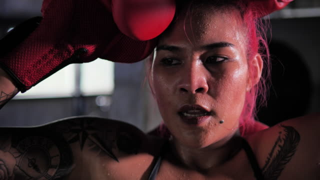 Boxer woman sitting lifting the corner of the boxing ring, Boxers Asian women with tattoos of red hair.